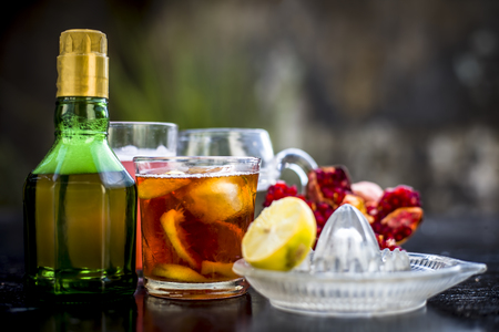 Pamosa or pomosa drink or classic mimosa drink in a transparent glass with champagne,pomegranate juice or annar ka juice,lemon juice,mint leaves,ice cubes and raw pomegranate and lemon,Close up view,