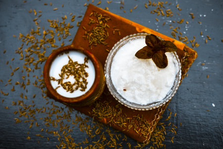 A clay glass full of buttermilk or chass or chhaachh with cumin seeds powder and raw cumin,slat and black pepper on wooden surface served after launch as cold drink with ice cubes,Top shot. Stockfoto