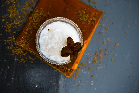 Curd with salt,black pepper and cumin powder with raw cumin on wooden surface with a glass full of water,ingredients of buttermilk or chass or chhaachh,Close up view or top shot.
