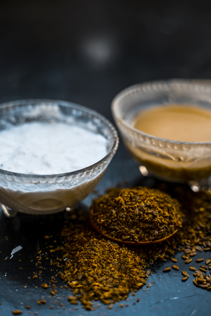 Home remedy for seborrhea dermatitis hair loss on wooden surface i.e. Curd with water and flax seed powder in a glass container with raw flax seed,Close up view.