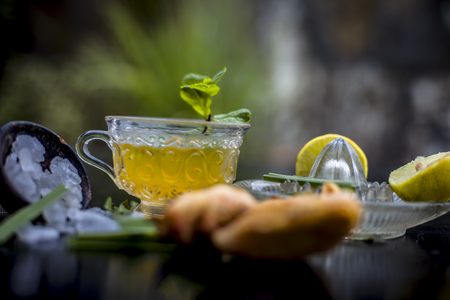 Close up of Iced lemon grass tea in a transparent cup on wooden surface with raw lemon grass green tea in a cup and sugar in a clay bowl with ice cubes in the cup and a piece of ginger and honey. Stock Photo
