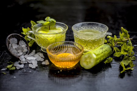Iced cucumber and mint tea on wooden surface in a transparent cup with slices of cucumber and raw cucumber,mint leaves,sugar and honey with green tea in a separate glass cup. Imagens