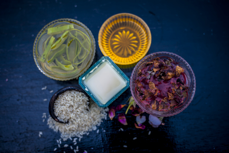 Close up of face pack of rice flour with honey and rose water on wooden surface in a glass container with rose water and rice flour used to clean acne and pimples.