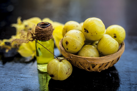 Close up of green colored herbal and organic oil of amla or Indian gooseberry in a transparent bottle with raw amla in a basket. Archivio Fotografico