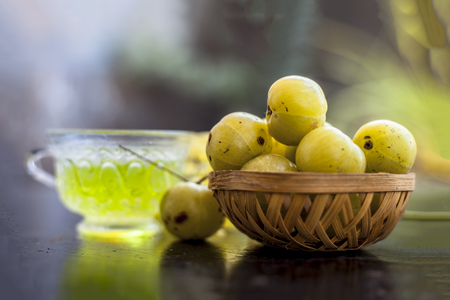 Close up of ayurvedic and organic tea of amla or Indian gooseberry in a transparent cup on wooden surface with raw amla in a fruit basket.