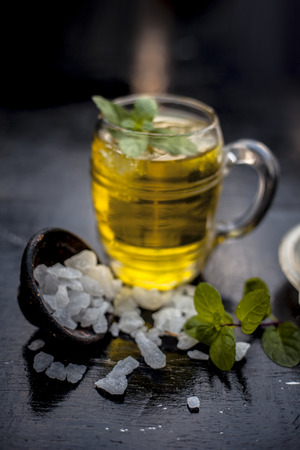 Close up of refreshing mint and lemon cooler in a transparent glass on wooden surface with raw lemon and juice and sugar.