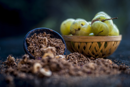 Close up of raw amla or Phyllanthus emblica or Indian gooseberry in a fruit basket with its dried seed powder in a clay bowl used in face pack,drinks and in natural medicines on wooden surface. Archivio Fotografico