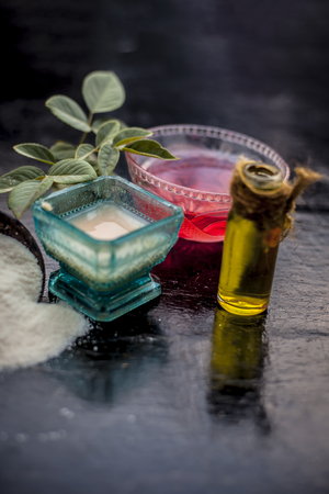 Close up of rice flour face pack on wooden surface in a blue colored glass bowl with some raw rose water,rice flour and Castor oil in a transparent bottle.Used to clear acne and pimples. Stock fotó