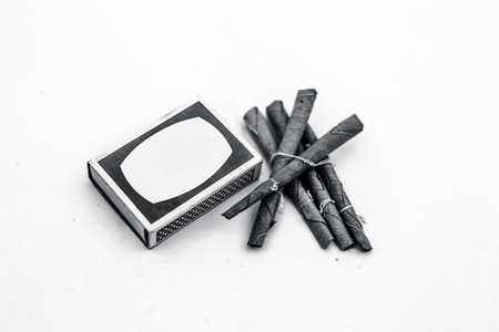 Close up of Mini cigar or mini cigarette or bidi or beedi isolated on white with a matchbox.
