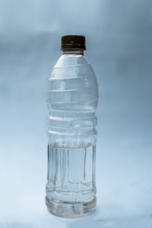 Plastic water bottle isolated on white or bluish background with having some water in it.Close up view.