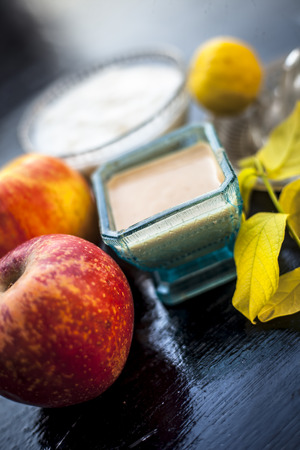 Close up of best home remedy or face pack for better skin complexion on wooden surface i.e. Apple pulp well mixed with lemon juice and curd.Top shot.