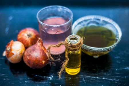 Close up of best hair therapy on wooden surface i.e. onion juice well mixed with organic olive oil.It boosts hair growth and fights dandruff and condition your hair and scalp.