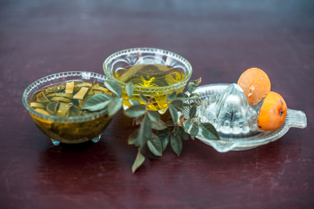 Close up of hair mask of aloe vera and lemon on wooden surface in a glass bowl with some raw aloe vera and lemon juice in glass vessels respectively.