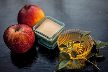 Close up of face pack of apple i.e. apple pulp mixed with honey to normalize skin which becomes dry in winter on wooden surface.; Stock Photo
