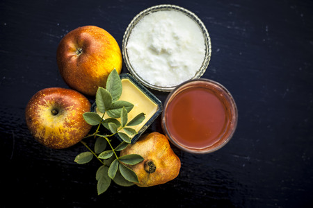 Instant grow therapy on wooden surface i.e. face pack of apple or pomegranate consisting of apple,curd or yogurt and pomegranate juice in a glass bowl,close up view.