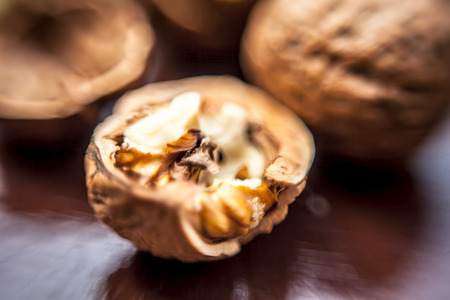 Macro shot of raw organic walnuts in sell on wooden surface. Banque d'images
