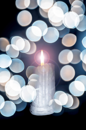 Close up of white colored wax candles with bokeh of Christmas lights.
