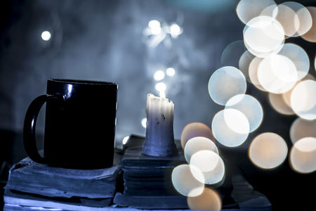 Close up of white colored wax candle with some blue light on it and black colored empty coffee mug with it on some brown colored old books and bookeh and light of Christmas.