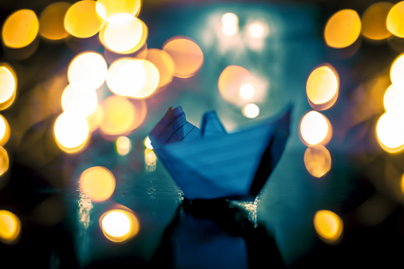 Close up of paper boat on wooden surface with reflection of Christmas decoration lights and decorative things. Stock Photo