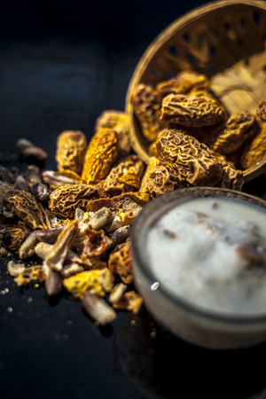 Close up of popular Indian and asian Winter drink on wooden surface i.e. Kharek ka dudh or dried dates milk consisting of milk,dried dates,cashews,almonds dry fruits and sugar. Imagens - 124596044