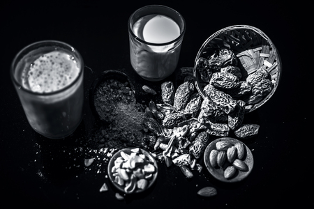 Close up of popular Indian and asian Winter drink on wooden surface i.e. Kharek ka dudh or dried dates milk consisting of milk,dried dates,cashews,almonds dry fruits and sugar. Imagens - 124596052