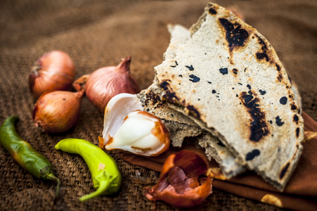 Close up of meal or lunch of villager or a typical farmer on gunny bag's background consisting of pearl millet's roti or chapati or bajra or bajri ki roti with some onions and chilies with it. Imagens - 124596053