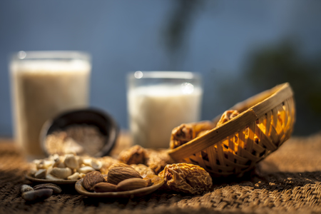 Close up of popular Indian and asian Winter drink on brown colroed gunny bag's surface i.e. Kharek ka dudh or dried dates milk consisting of milk,dried dates,cashews,almonds dry fruits and sugar. Imagens - 124596086