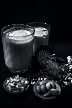 Close up of popular Indian and asian Winter drink on wooden surface i.e. Kharek ka dudh or dried dates milk consisting of milk,dried dates,cashews,almonds dry fruits and sugar.