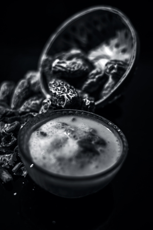 Close up of popular Indian and asian Winter drink on wooden surface i.e. Kharek ka dudh or dried dates milk consisting of milk,dried dates,cashews,almonds dry fruits and sugar. Imagens - 124596292