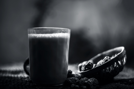Close up of popular Indian and asian Winter drink on brown colroed gunny bag's surface i.e. Kharek ka dudh or dried dates milk consisting of milk,dried dates,cashews,almonds dry fruits and sugar. Imagens - 124596298