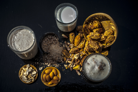 Close up of popular Indian and asian Winter drink on wooden surface i.e. Kharek ka dudh or dried dates milk consisting of milk,dried dates,cashews,almonds dry fruits and sugar. Фото со стока - 124596307