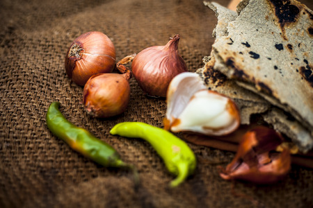 Close up of meal or lunch of villager or a typical farmer on gunny bag's background consisting of pearl millet's roti or chapati or bajra or bajri ki roti with some onions and chilies with it. Фото со стока - 124596329