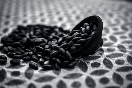 Close up of brown colored dried custard apples or sitaphal or sugar apple seeds in a black colored clay bowl on a brown colored surface. Фото со стока - 124596331