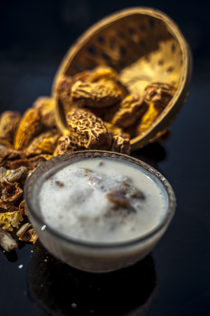 Close up of popular Indian and asian Winter drink on wooden surface i.e. Kharek ka dudh or dried dates milk consisting of milk,dried dates,cashews,almonds dry fruits and sugar. Фото со стока - 124596333