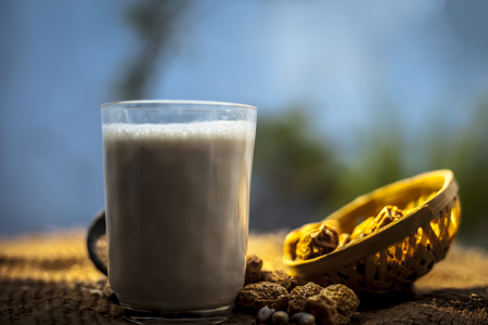 Close up of popular Indian and asian Winter drink on brown colroed gunny bag's surface i.e. Kharek ka dudh or dried dates milk consisting of milk,dried dates,cashews,almonds dry fruits and sugar. Imagens - 124596338