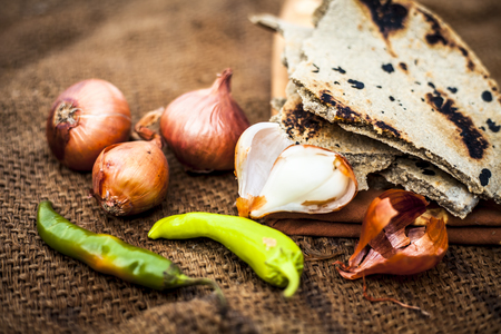 Close up of meal or lunch of villager or a typical farmer on gunny bags background consisting of pearl millets roti or chapati or bajra or bajri ki roti with some onions and chilies with it.