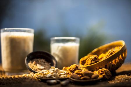 Close up of popular Indian and asian Winter drink on brown colroed gunny bag's surface i.e. Kharek ka dudh or dried dates milk consisting of milk,dried dates,cashews,almonds dry fruits and sugar. Imagens - 124596348