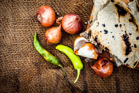 Close up of meal or lunch of villager or a typical farmer on gunny bag's background consisting of pearl millet's roti or chapati or bajra or bajri ki roti with some onions and chilies with it. Фото со стока - 124596368