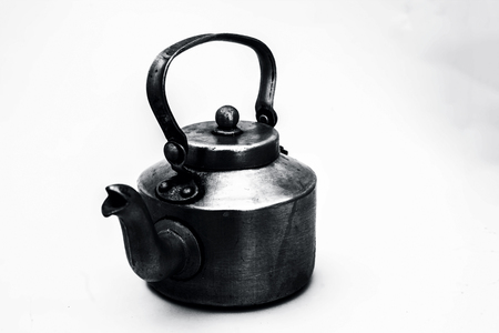 Close up of shiny silver colored steel kettle isolated on white used to serve tea or coffee.
