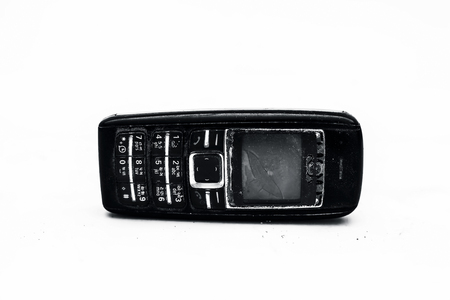 Close up of a black colored old cell phone with black colored body and broken switches and screen isolated on white. Banque d'images