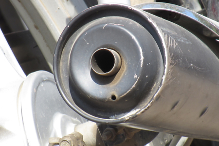 Close up of black and white colored steel and plastic silencer of typical common Indian bike on the roads.