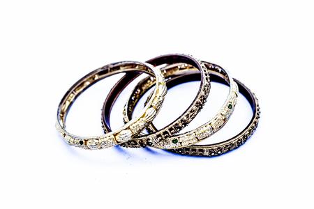Nahaufnahme von goldfarbenen Metallarmreifen isoliert auf weiss mit einigen Diamanten darauf.