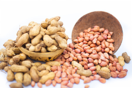 Raw organic groundnut or peanuts isolated on white with raw peanuts in a hamper with peanuts in clay bowl.