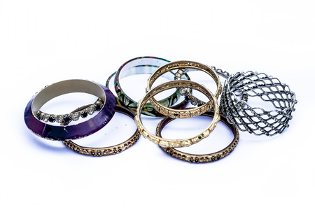Close up of mixed ornaments or jeweleries to wear them in hands isolated on white which are bangles and some other band like objects.