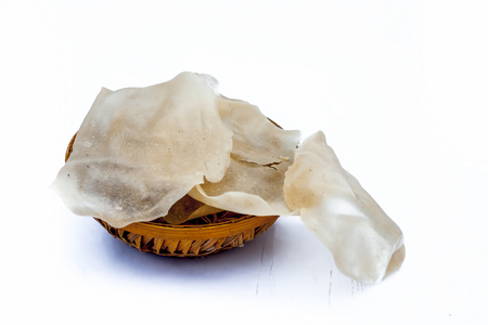 Popular Indian and Asian crispy snack dish i.e. Raw uncooked Papad or rice flour papadum in  a hamper isolated on white.