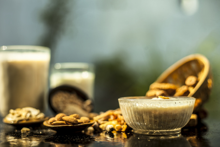 Close up of popular Indian and asian Winter drink on brown colored gunny bags surface i.e. Kharek ka dudh or dried dates milk consisting of milk,dried dates,cashews,almonds dry fruits and sugar. Imagens