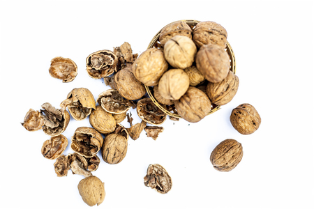 Close up of raw organic Walnut or Juglans or Akhrot or Akharot isolated on white in a hamper without shell on surface. Stock Photo - 122952905