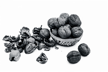 Close up of raw organic Walnut or Juglans or Akhrot or Akharot isolated on white in a hamper without shell on surface. Stock Photo