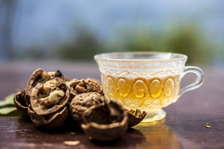 Close up of herbal organic tea of wall nut or walnut tea in a transparent glass cup with raw wall nut in shell and broken also.