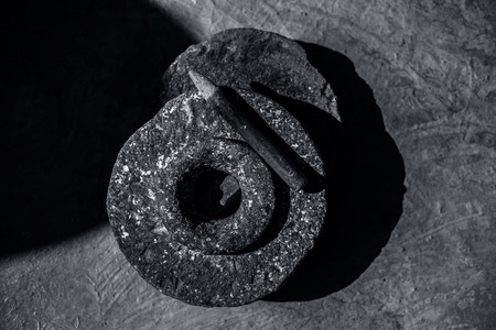 Close up of hand grinding stone or hand grinder or old motor or pestle or grain mills on rough surface still used in some of the villages of Asia and India. Archivio Fotografico
